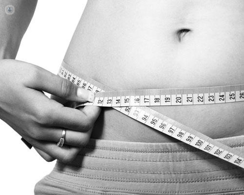 Chica mostrando la tripa y midiendo la reducción - bypass gástrico - by Top Doctors