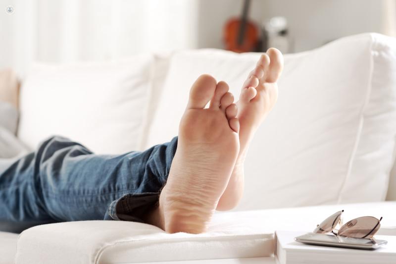 Hombre en un sofá mostrando los pies - neuroma de Morton - by Top Doctors