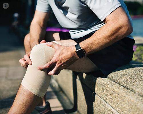 Hombre sentado con una rodillera y tocándose la rodilla - fisioterapia deportiva - by Top Doctors